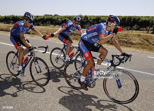 Floyd Landis of the United States, center, and riding for US Postal Service-Berry Floor performs his domestique duties as he delivers water to...