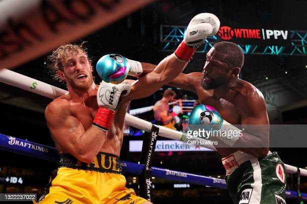 Floyd Mayweather exchanges blows with Logan Paul during their contracted exhibition boxing match at Hard Rock Stadium on June 06, 2021 in Miami...