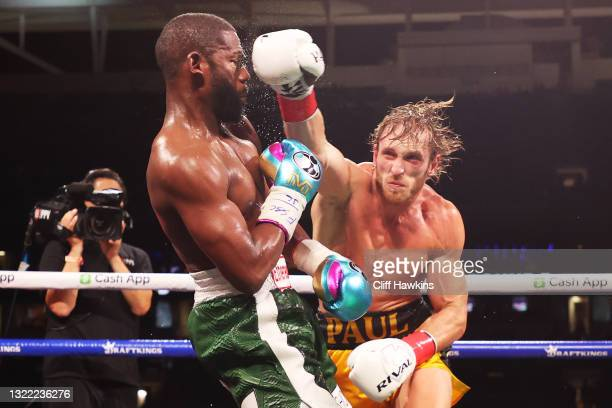 Floyd Mayweather is punched by Logan Paul during their contracted exhibition boxing match at Hard Rock Stadium on June 06, 2021 in Miami Gardens,...