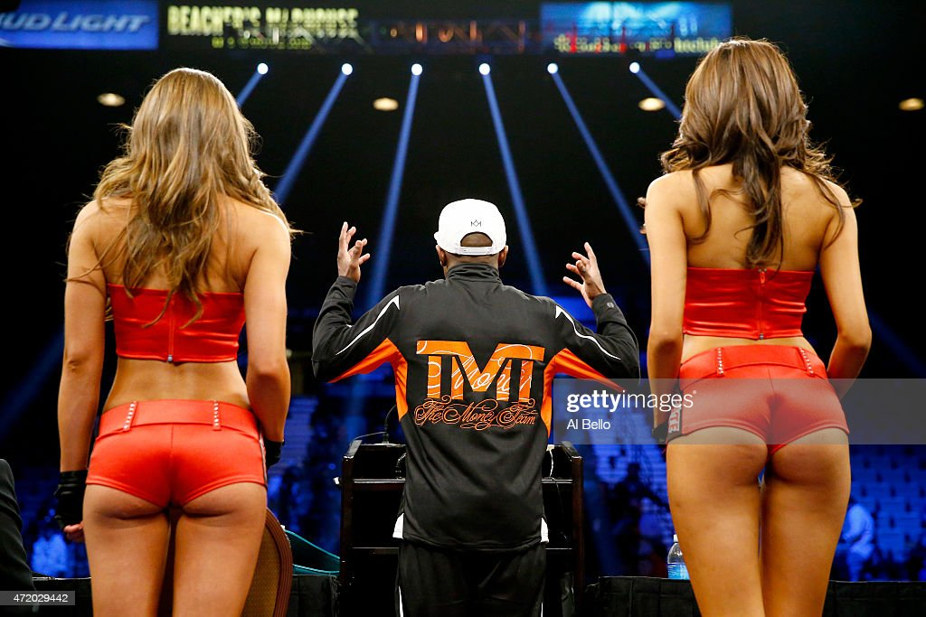 Floyd Mayweather Jr. addresses the media as he stands between the Tecate girls during the post-fight news conference after his unanimous decision victory against Manny Pacquiao in their welterweight unification championship bout on May 2, 2015 at MGM Grand Garden Arena in Las Vegas, Nevada.