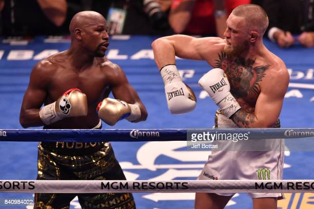 Floyd Mayweather Jr and Conor McGregor exchange punches in their super welterweight boxing match at TMobile Arena on August 26 2017 in Las Vegas...