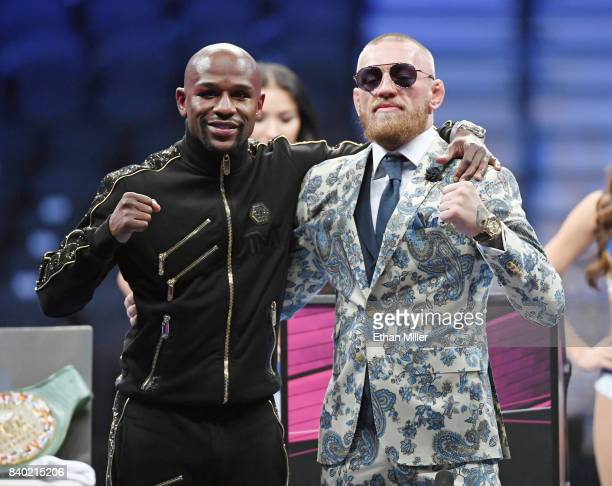 Floyd Mayweather Jr and Conor McGregor pose for pictures during a news conference after Mayweather's 10thround TKO victory in their super...