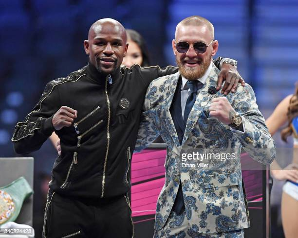 Floyd Mayweather Jr. And Conor McGregor pose for pictures during a news conference after Mayweather's 10th-round TKO victory in their super...