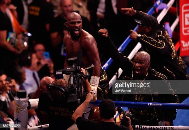 Floyd Mayweather Jr and Floyd Mayweather Sr celebrate after defeating Conor McGregor by TKO in the 10th round during their super welterweight boxing...