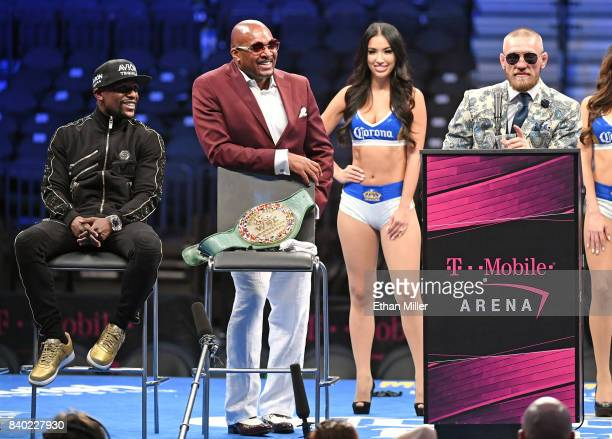 Floyd Mayweather Jr and Mayweather Promotions CEO Leonard Ellerbe look on as Conor McGregor speaks during a news conference after Mayweather defeated...