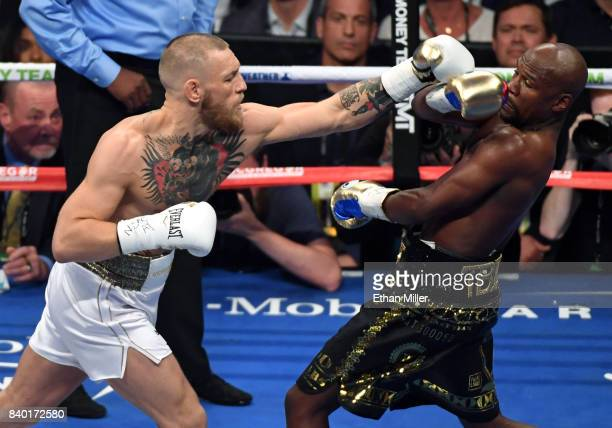 Floyd Mayweather Jr avoids a punch from Conor McGregor in the first round of their super welterweight boxing match at TMobile Arena on August 26 2017...
