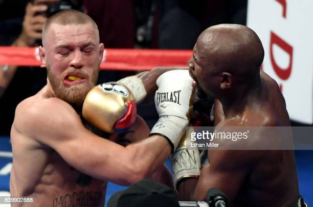 Floyd Mayweather Jr hits Conor McGregor in the ninth round of their super welterweight boxing match at TMobile Arena on August 26 2017 in Las Vegas...