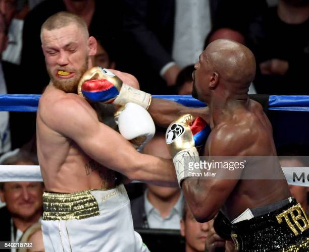 Floyd Mayweather Jr hits Conor McGregor with a right in the 10th round of their super welterweight boxing match at TMobile Arena on August 26 2017 in...