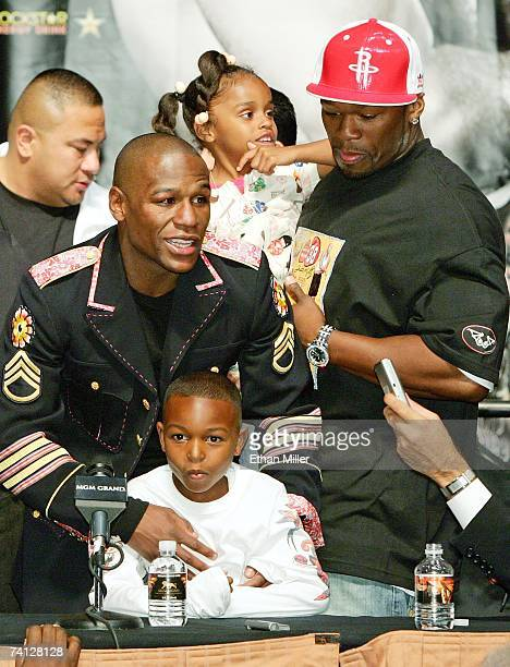 Floyd Mayweather Jr holds his son Koraun Mayweather while rapper 50 Cent holds Mayweather's daughter Iyanna Mayweather during a news conference after...