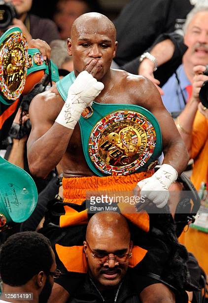 Floyd Mayweather Jr is carried in the ring by CEO of Mayweather Promotions Leonard Ellerbe as they celebrate Mayweather's fourthround knockout of...