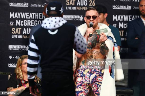 Floyd Mayweather Jr looks on as Conor McGregor holds a dollar bill during the Floyd Mayweather Jr v Conor McGregor World Press Tour event at Barclays...