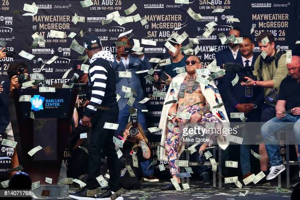 Floyd Mayweather Jr looks on as money rains down on Conor McGregor during the Floyd Mayweather Jr v Conor McGregor World Press Tour event at Barclays...