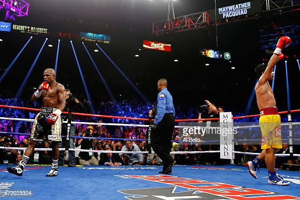 Floyd Mayweather Jr Manny Pacquiao react after the twelfth round during their welterweight unification championship bout on May 2 2015 at MGM Grand...