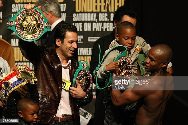 Floyd Mayweather Jr picks up his son Koraun Mayweather as IRL driver Helio Castroneves holds onto two of Mayweather's belts during the weighin for...
