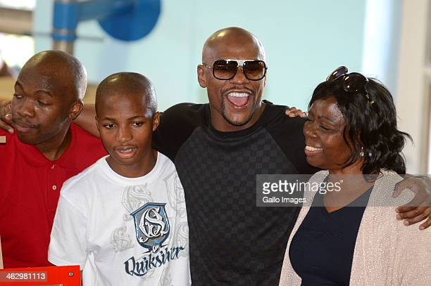 Floyd Mayweather Jr poses with Baby Jake Matlala's wife Mapula and sons Tshepo and Masego during his visit to Dube Boxing Gym on January 16 2014 in...