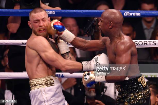 Floyd Mayweather Jr punches Conor McGregor in their super welterweight boxing match at TMobile Arena on August 26 2017 in Las Vegas Nevada Mayweather...
