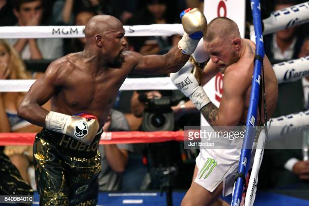 Floyd Mayweather Jr. Punches Conor McGregor in their super welterweight boxing match at T-Mobile Arena on August 26, 2017 in Las Vegas, Nevada....