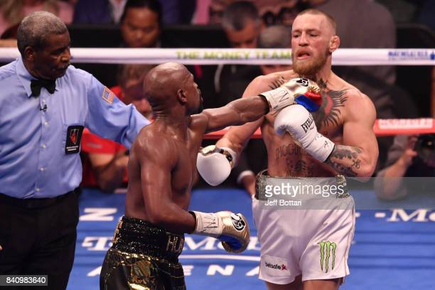 Floyd Mayweather Jr pushes Conor McGregor after the bell rings in their super welterweight boxing match at TMobile Arena on August 26 2017 in Las...