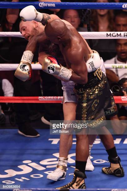 Floyd Mayweather Jr pushes Conor McGregor with his forearm in their super welterweight boxing match at TMobile Arena on August 26 2017 in Las Vegas...