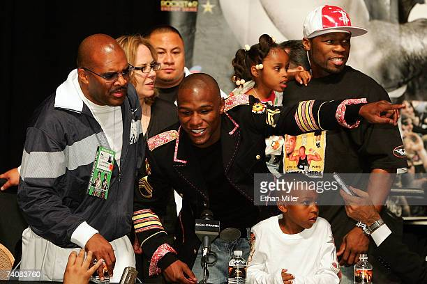 Floyd Mayweather Jr speaks to the press as his manager Leonard Ellerbe looks on while rapper 50 Cent holds Mayweather's daughter Iyanna behind...