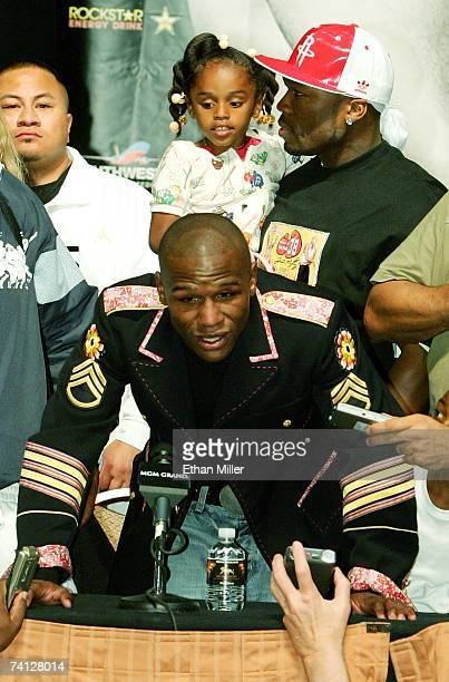 Floyd Mayweather Jr talks to members of the media while rapper 50 Cent holds Mayweather's daughter Iyanna Mayweather during a news conference after...