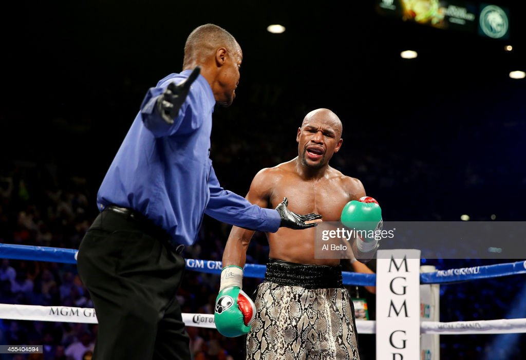 Floyd Mayweather Jr. tells referee Kenny Bayless that Marcos Maidana bit him during the 8th round in their WBC/WBA welterweight title fight at the MGM Grand Garden Arena on September 13, 2014 in Las Vegas, Nevada.