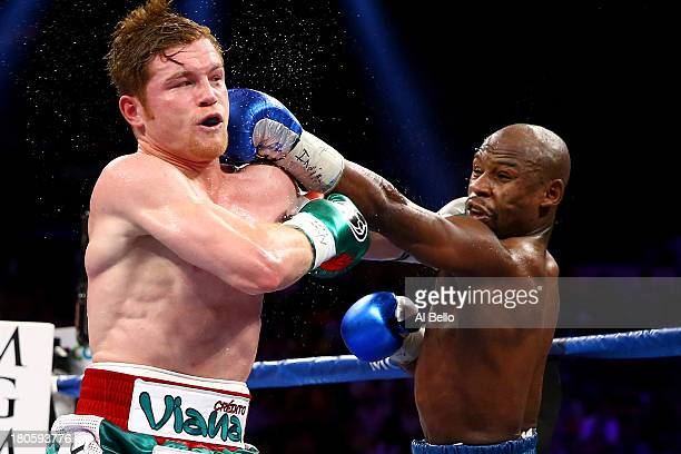 Floyd Mayweather Jr. Throws a left to the head of Canelo Alvarez during their WBC/WBA 154-pound title fight at the MGM Grand Garden Arena on...
