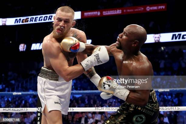 Floyd Mayweather Jr. Throws a punch at Conor McGregor during their super welterweight boxing match on August 26, 2017 at T-Mobile Arena in Las Vegas,...