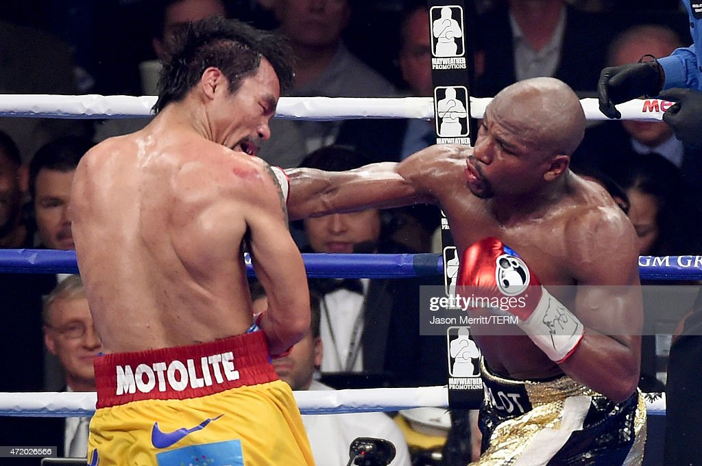 Floyd Mayweather Jr. (R) throws a right at Manny Pacquiao during their welterweight unification championship bout on May 2, 2015 at MGM Grand Garden Arena in Las Vegas, Nevada.