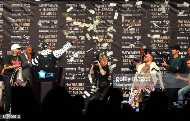 Floyd Mayweather Jr throws money in the air over Conor McGregor during the Floyd Mayweather Jr v Conor McGregor World Press Tour event at Barclays...