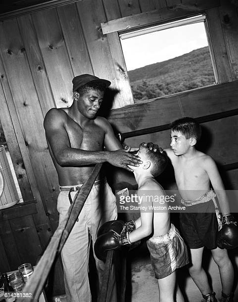 Floyd Patterson takes some time out of training to coach a couple of young boys and apply some vaseline to one of the young boys at his training camp...