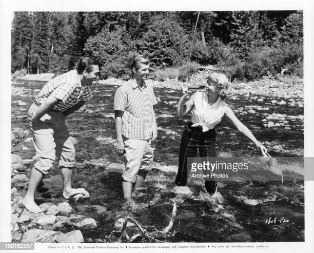 Floyd Simmons and Glen Kramer watch as Dorothy Malone tries to fish with her shoe in publicity portrait for the film 'Pillars Of The Sky' 1956
