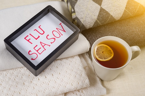 Flu season text in frame. Background warm woolen clothes, cup of hot tea. 1001718898