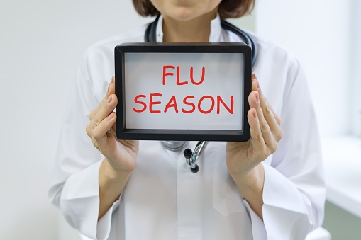 Flu season text in the hands of a female doctor 1023923268