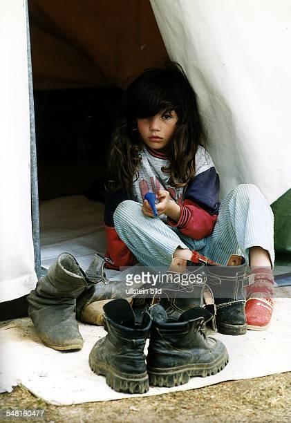 Flucht und Vertreibung der albanischen Bevölkerung aus dem Kosovo: Flüchtlingslager Stenkovic Kleines Mädchen vor einem Zelt.