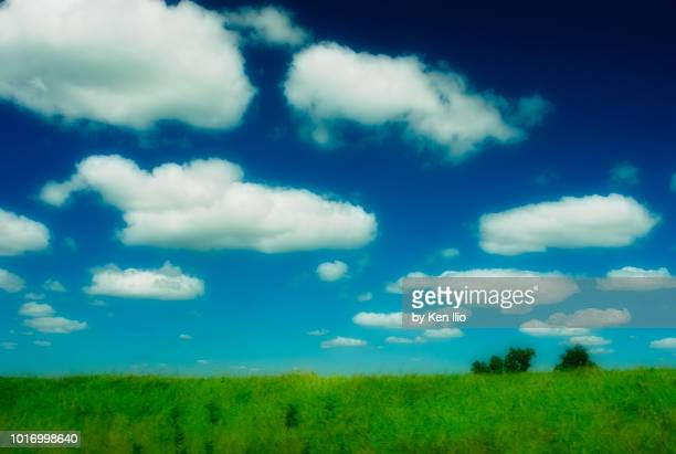 fluffy clouds against blue sky - ken ilio stock photos and pictures