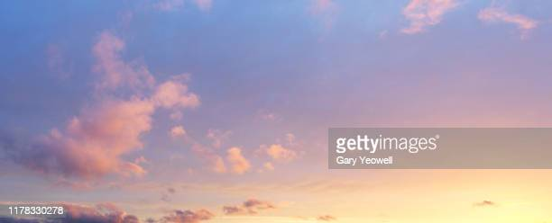 fluffy clouds at sunset - avondschemering stockfoto's en -beelden
