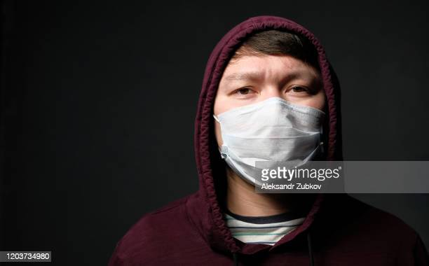 a flu-infected asian man wearing a medical mask that protects him from the coronavirus. the concept of air pollution, pneumonia outbreaks, epidemics, and the danger of viral infection. - coronavirus stock pictures, royalty-free photos & images