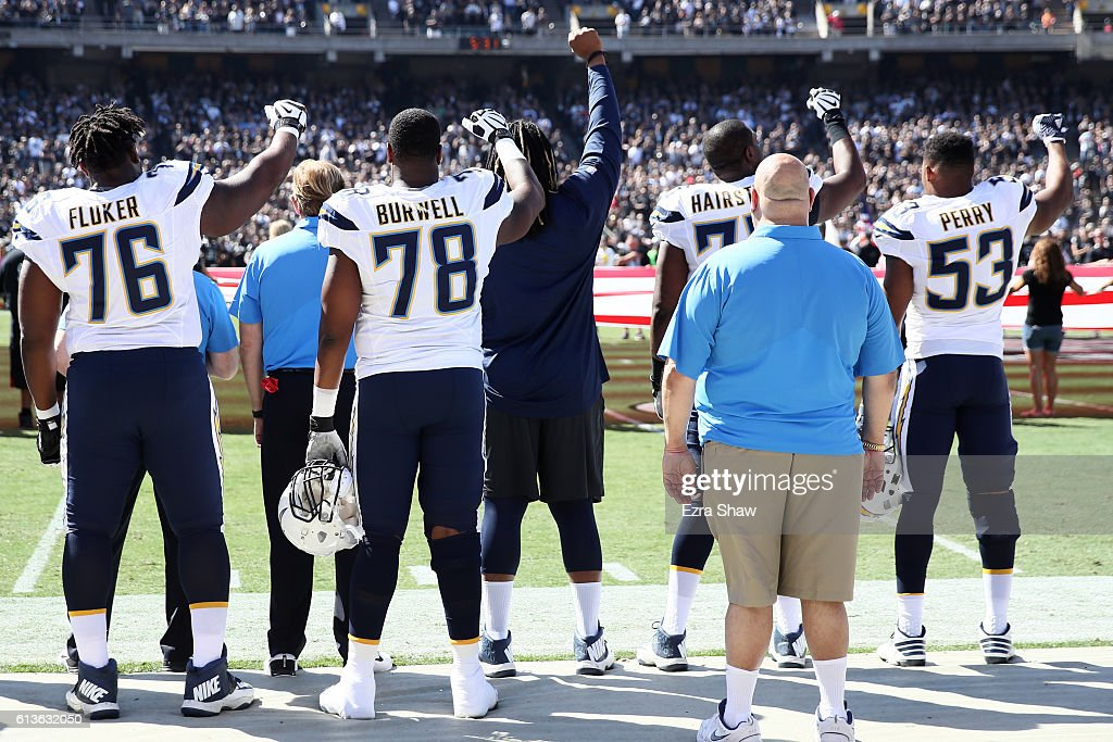 D.J. Fluker #76, Tyreek Burwell #78, Chris Hairston #75 and Joshua Perry #53 of the San Diego Chargers raise their fists in protest during the national anthem prior to their NFL game against the Oakland Raiders at Oakland-Alameda County Coliseum on October 9, 2016 in Oakland, California.