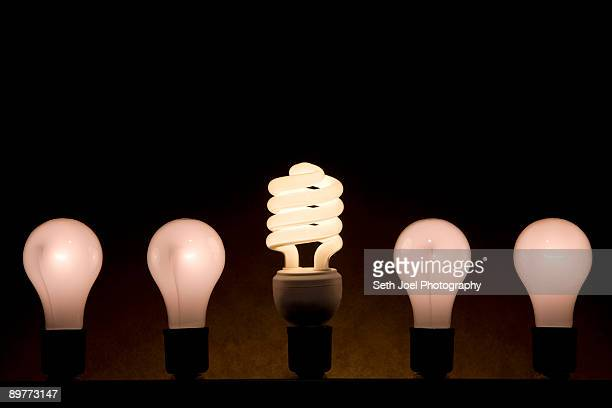 fluorescent and incandescent light bulbs - putting stock pictures, royalty-free photos & images