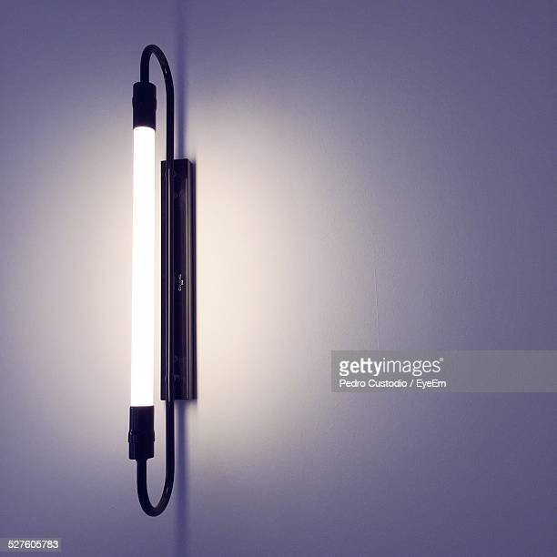 fluorescent sconce on white wall - fluorescent light stock pictures, royalty-free photos & images
