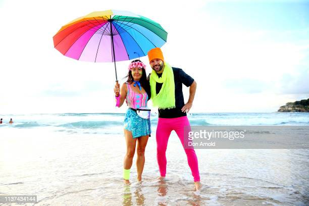 A fluro clad Jodi Hooker and Phil Conway pose on the Bondi Beach shoreline on March 22 2019 in Sydney Australia Surfers gather to celebrate five...