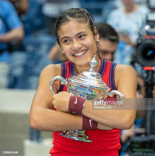 Tennis champion Emma Raducanu hugging her trophy in disbelief after defeating Leylah Fernandez in the women's finals and receiving $2.5 million at...
