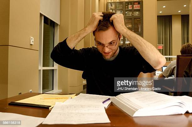 Flustered college student grabs his hair as he looks at his notes in the Reading Room of the Brody Learning Commons, a study space and library on the...