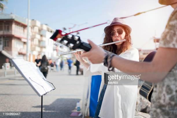 flötist und ihr gitarrist spielen auf der straße - straßenmaler stock-fotos und bilder