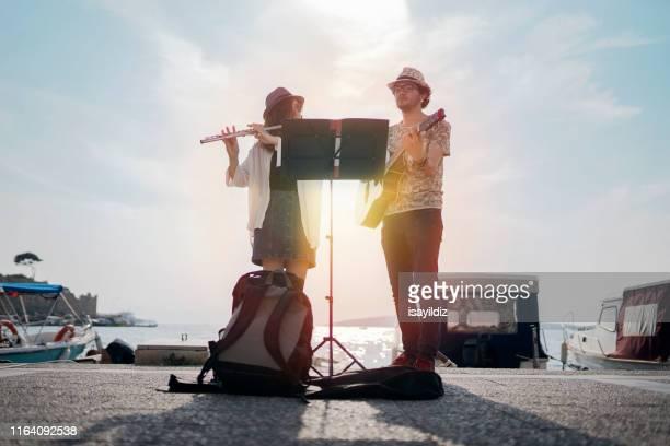 flutist y su amigo guitarrista están tocando en la calle - músico fotografías e imágenes de stock
