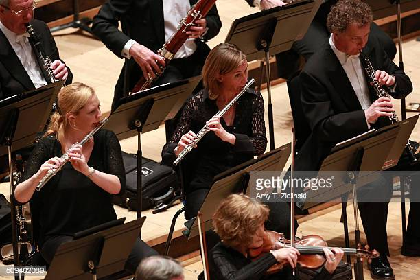 Flutists perform as English pianist Stephen Hough plays at the piano as Finnish conductor Osmo Vanska leads the London Philharmonic Orchestra in...