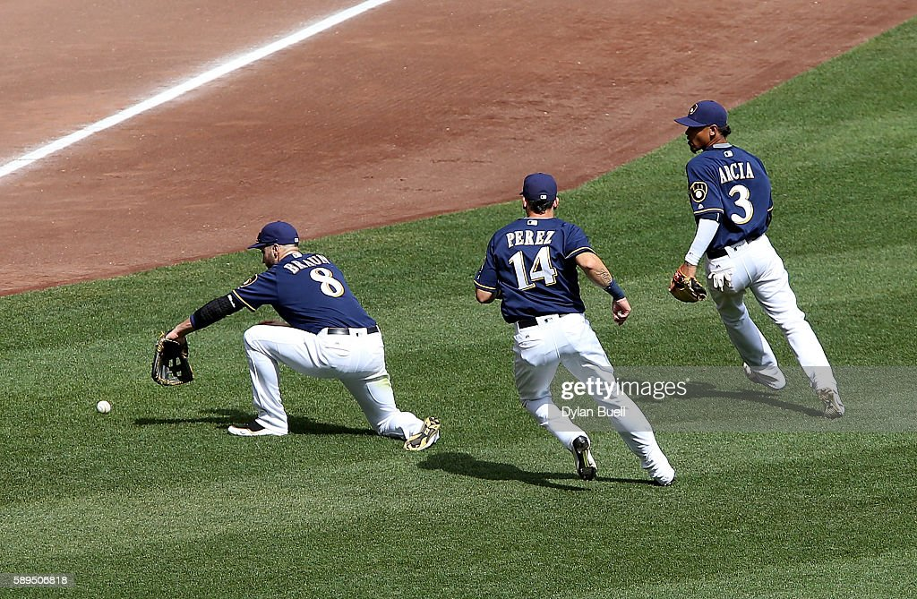 A fly ball drops between Ryan Braun #8, Hernan Perez #14, and Orlando Arcia #3 of the Milwaukee Brewers in the sixth inning against the Cincinnati Reds at Miller Park on August 14, 2016 in Milwaukee, Wisconsin.
