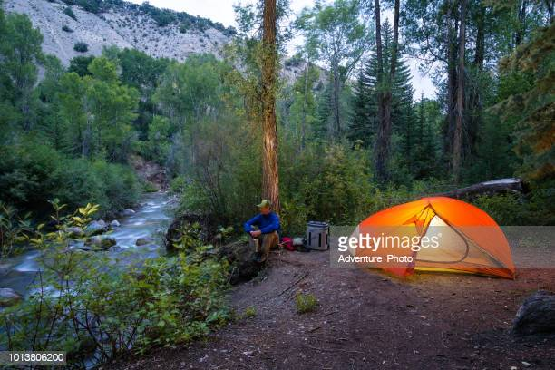 fly fish backcountry camp along creek - yeti stock photos and pictures