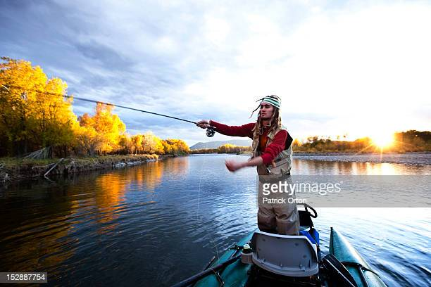 a fly fisher casting his line out of a boat while fly fishing surrounded by fall colors in montana. - fly casting stock pictures, royalty-free photos & images